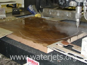 waterjet cutting in progress cutting thick Peruvian maple wood.
